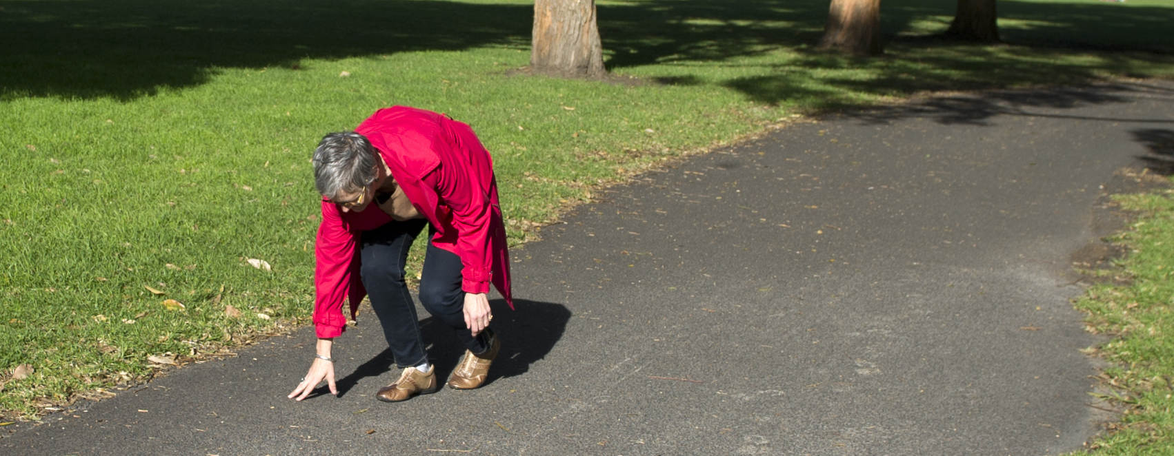 Older lady stumbles on park pathway
