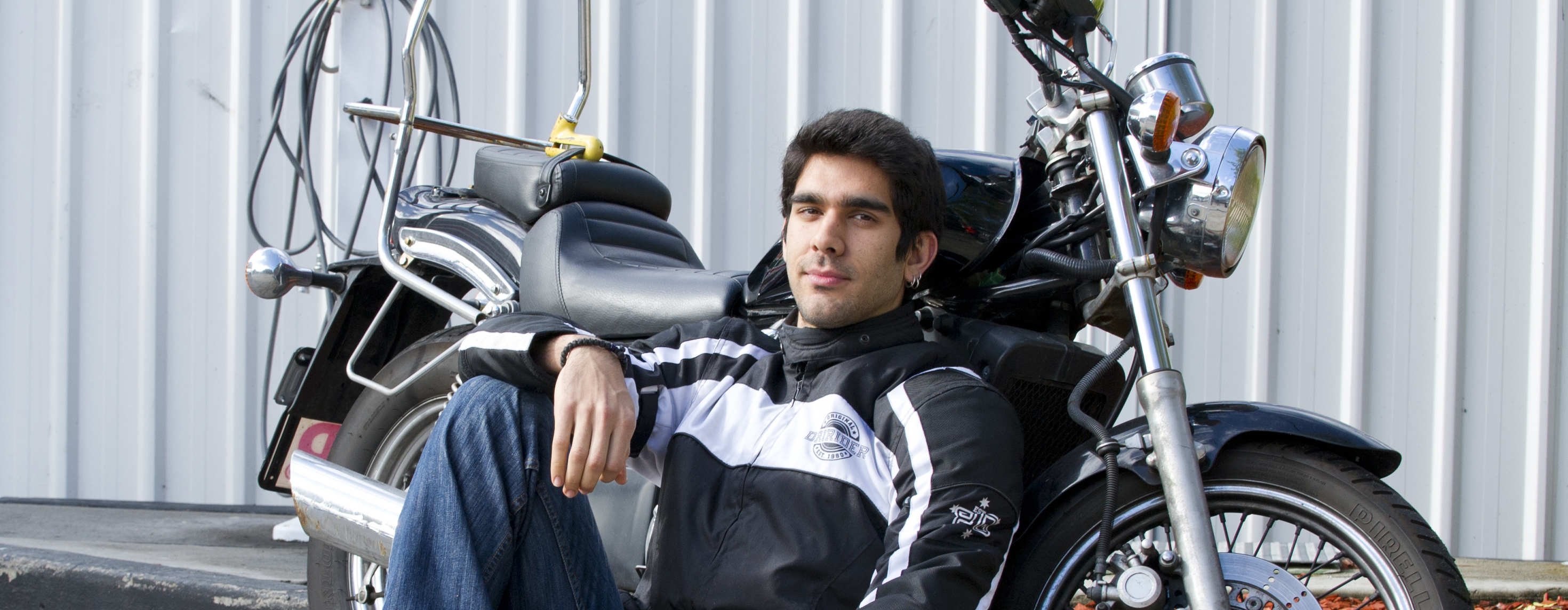 Young man leans against motorcycle