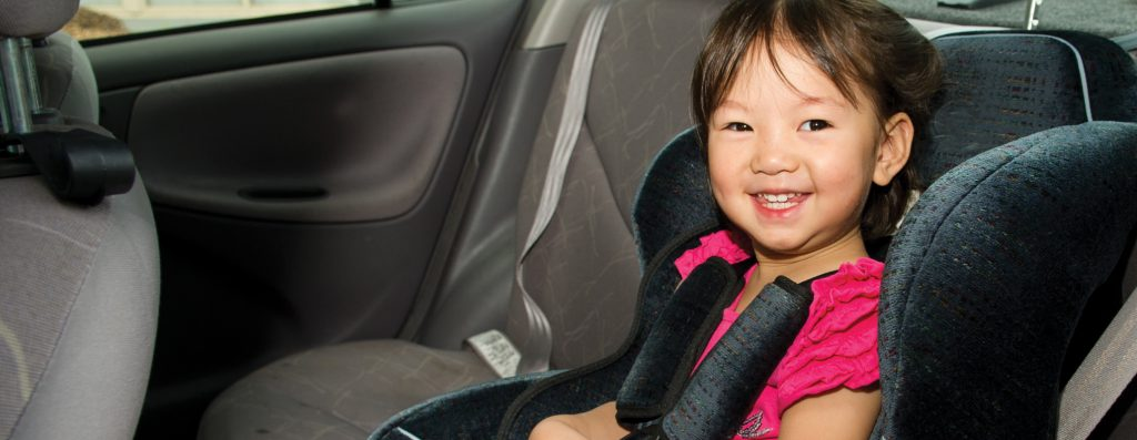 Young girl in rear seat child restraint