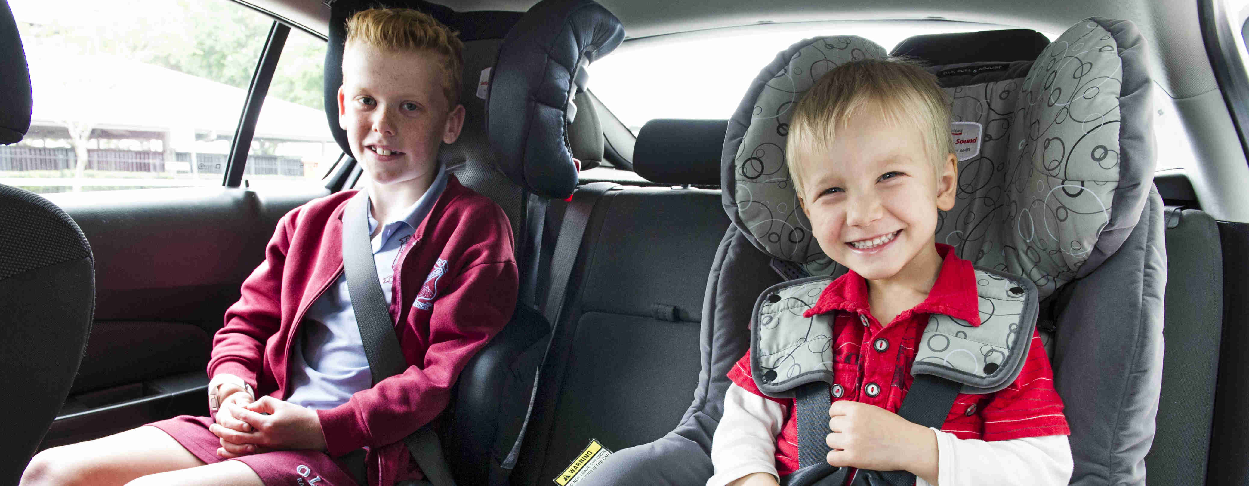 Two young boys in child restraint seats