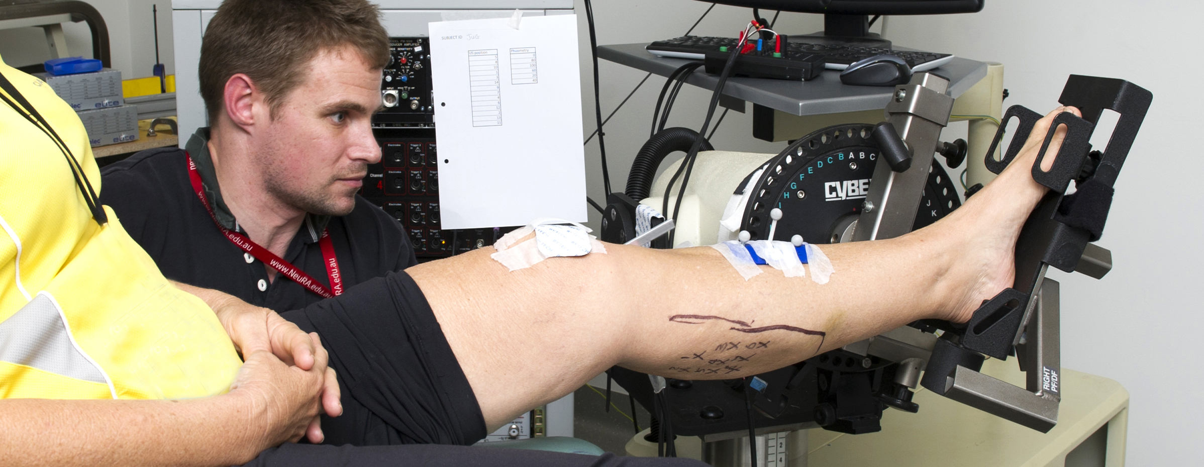 Researcher with participant's leg in study on muscle contracture