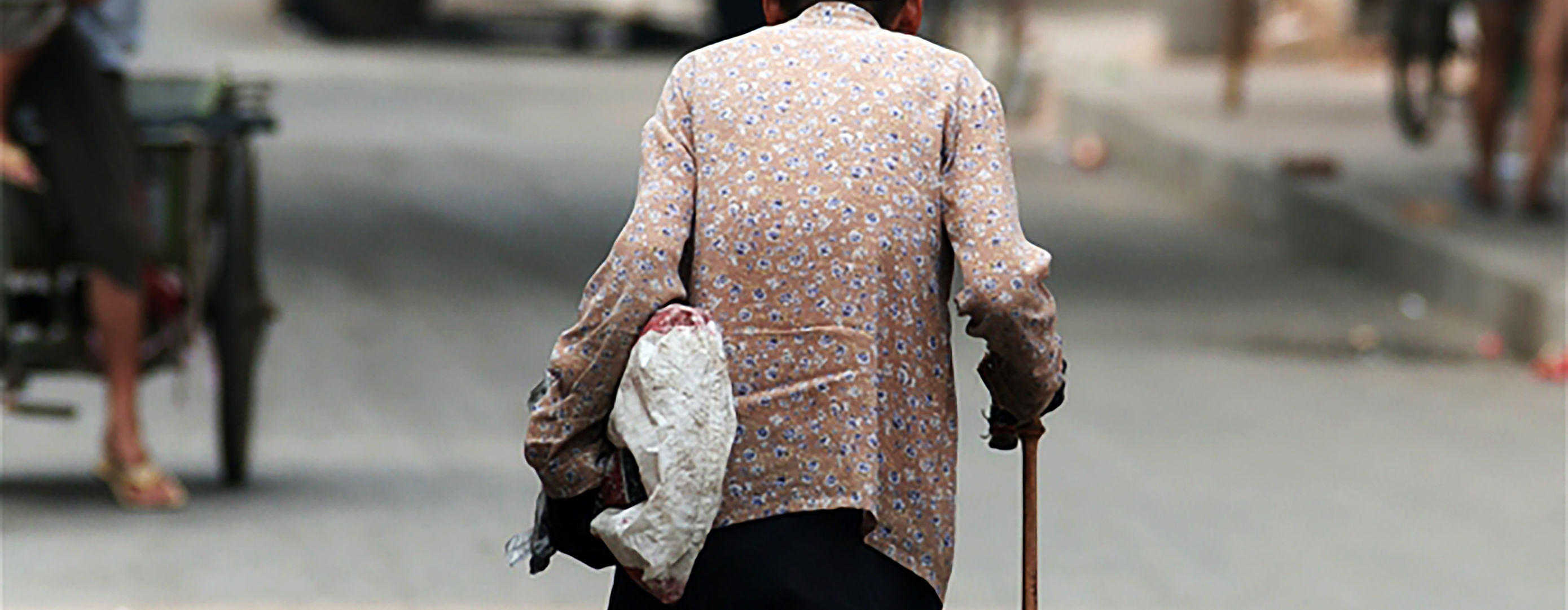 Older lady walking along street with cane