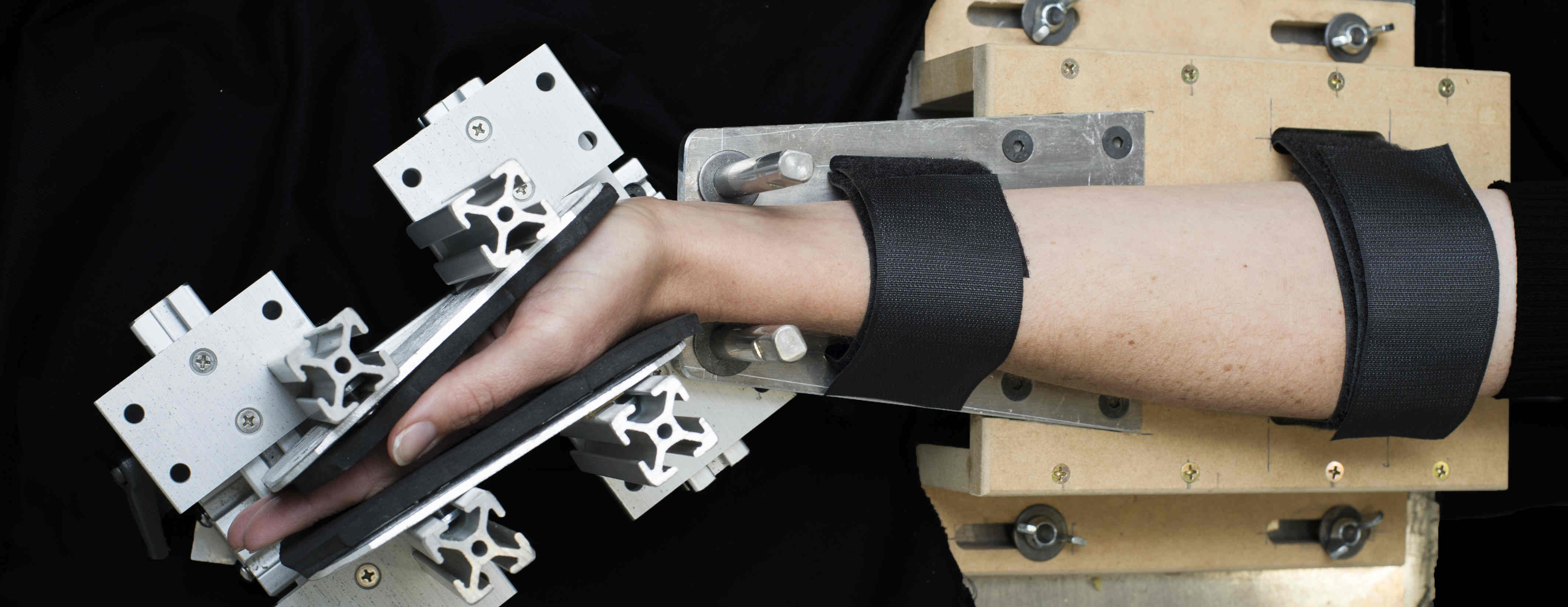 Research participant's arm in a machine designed for motor impairment study